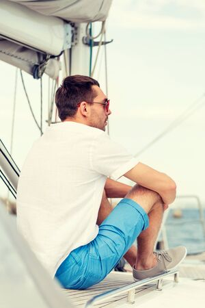 tripping: vacation, holidays, travel, sea and people concept - man in sunglasses sitting on yacht deck