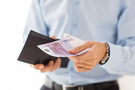 money euro: people, business, finances and money concept - close up of businessman hands holding open wallet with euro cash Stock Photo
