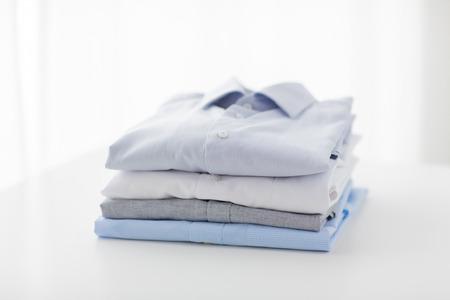 plancha, lavandería, ropa, limpieza y objetos concepto - cerca de camisas planchadas y dobladas sobre la mesa en casa Foto de archivo
