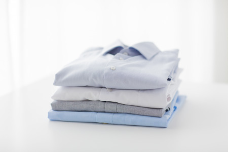 ironing, laundry, clothes, housekeeping and objects concept - close up of ironed and folded shirts on table at home Archivio Fotografico
