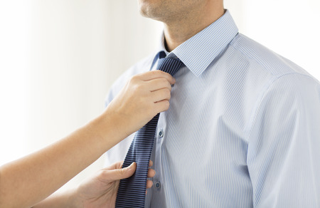 formal dressing: people, business, care and clothing concept - close up of woman helping man and adjusting tie on his neck at home Stock Photo