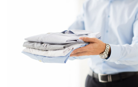 folded hands: business, clothing and people concept - close up of businessman holding folded shirts