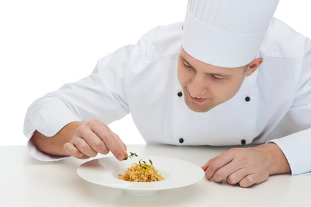 cooking, profession, haute cuisine, food and people concept - happy male chef cook decorating dish Stock Photo