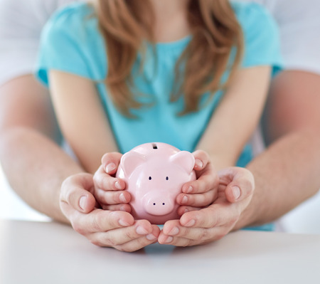family, children, money, investments and people concept - close up of father and daughter hands holding pink piggy bank Foto de archivo