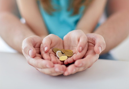 investing: family, children, money, investments and people concept - close up of father and daughter hands holding euro money coins