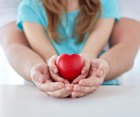 help people: people, charity, family and advertisement concept - close up of father and girl holding red heart shape in cupped hands at home