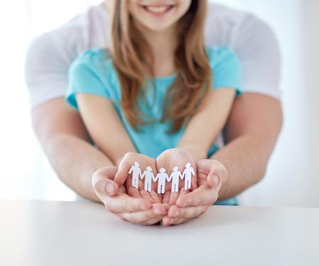 demografia: la gente, la caridad, la demografía y la familia concepto - cerca de padre y niña de la celebración del recorte humano en las manos ahuecadas en el hogar Foto de archivo
