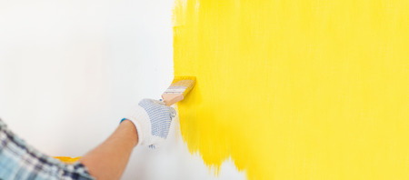home renovation: repair and home renovation concept - close up of male hand in gloves painting a wall with yellow paint