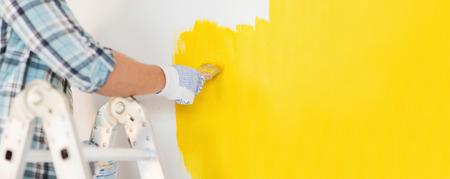 HOMBRE PINTANDO: reparación y rehabilitación de viviendas concepto - cerca de la mano masculina en los guantes que pintan una pared con pintura amarilla