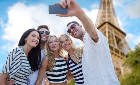 여름, 프랑스, 관광, 기술과 사람들 개념 - 파리 배경에서 에펠 탑을 통해 스마트 폰으로 셀카를 복용 친구 미소의 그룹 스톡 콘텐츠