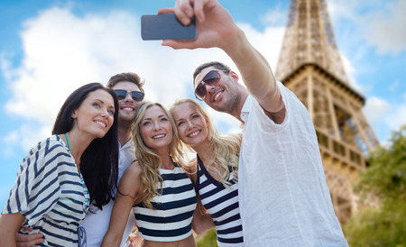summer, france, tourism, technology and people concept - group of smiling friends taking selfie with smartphone over eiffel tower in paris background Standard-Bild