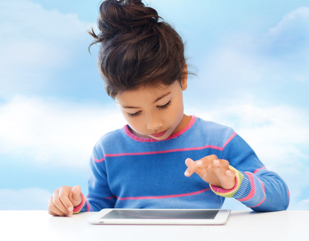 asian preteen: leisure, childhood, technology and people concept - little girl with tablet pc over blue sky background
