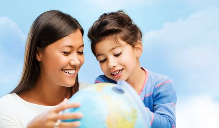 asian preteen: family, children, travel, geography and happy people concept - mother and daughter with globe over blue sky background