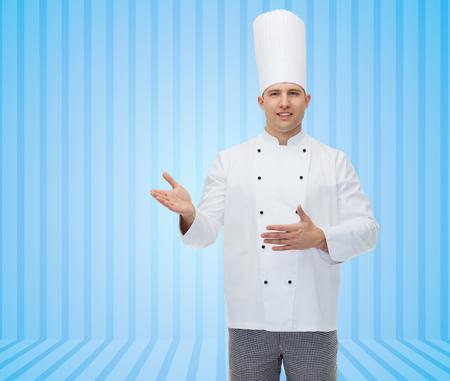 invitando: la cocina, la profesi�n y la gente concepto - feliz cocinero de sexo masculino cocinar invitando sobre fondo azul de rayas