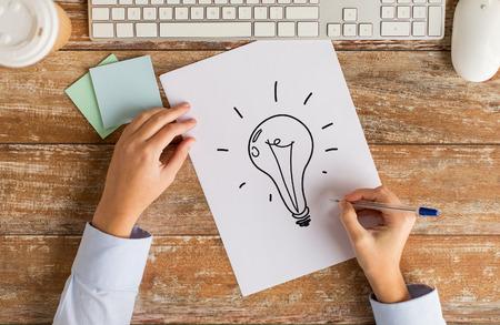 Wirtschaft, Bildung, Ideen, Inspiration und Personen-Konzept - Nahaufnahme der weiblichen Hände mit Bleistift und Computer-Tastatur Zeichnung Glühlampe auf Papierblatt