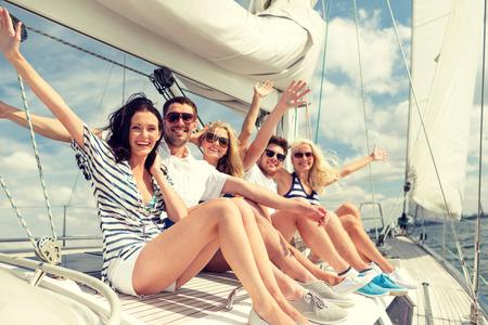 旅行: 度假,旅遊,海,友誼和人的概念 - 微笑的朋友坐在遊艇甲板和問候
