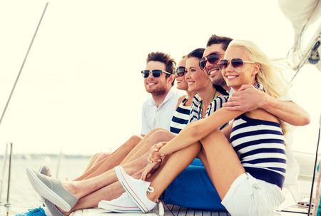 vacation, travel, sea, friendship and people concept - smiling friends sitting on yacht deck