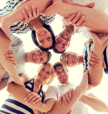 joining hands: friendship, happiness and people concept - smiling friends in circle