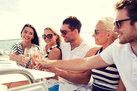 boat party: vacation, travel, sea, friendship and people concept - smiling friends with glasses of champagne on yacht