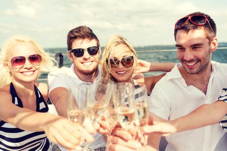 personas festejando: vacaciones, viaje, mar, la amistad y la gente concepto - amigos sonrientes con copas de champán en el yate Foto de archivo