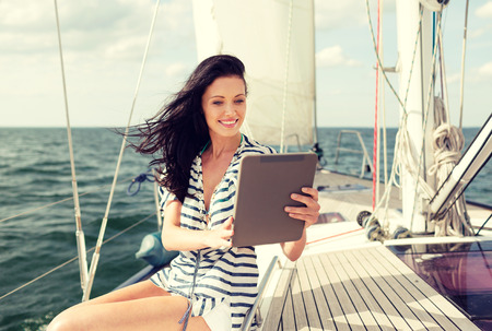 yacht people: vacation, holidays travel, sea and technology concept - smiling woman sitting on yacht with tablet pc