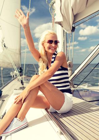 personas saludandose: vacaciones, días de fiesta, los viajes, el mar y la gente concepto - sonriente mujer joven sentada en la cubierta del yate y el saludo