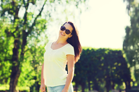 leasure: summer, leasure, vacation and people concept - smiling young woman wearing sunglasses standing in park