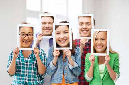 comunicacion no verbal: personas, emociones y comunicación concepto - grupo de amigos o estudiantes que cubren la cara con las hojas de papel Foto de archivo