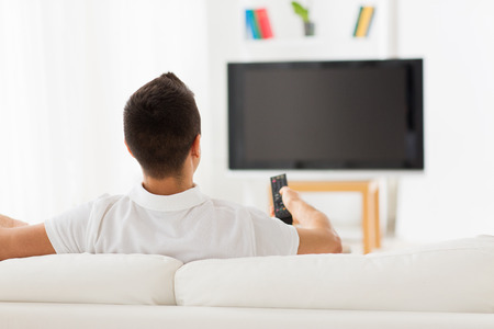 leisure, technology, mass media and people concept - man watching tv and changing channels at home from back Banque d'images