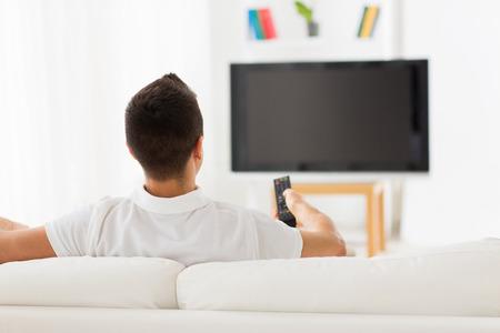 personas viendo television: ocio, tecnología, medios de comunicación y la gente concepto - hombre viendo la televisión y cambiar de canal en el hogar de la parte posterior
