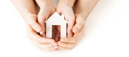 home insurance: real estate and family home concept - closeup picture of male and female hands holding white blank paper house
