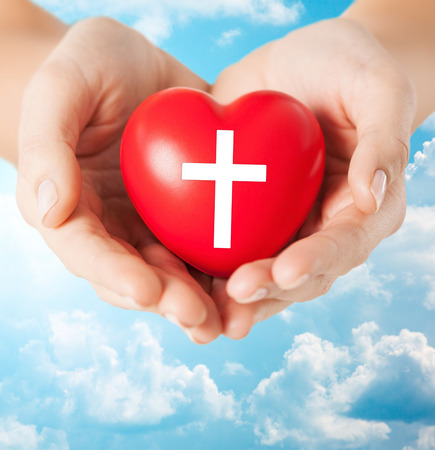 hope background: religion, christianity and charity concept - close up of female hands holding red heart with christian cross symbol over blue sky and clouds background