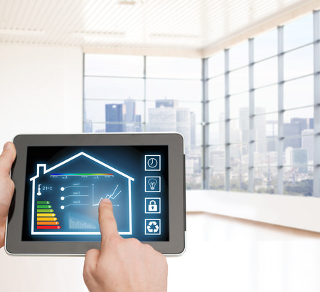 smart home: home, housing, people and technology concept - close up of man hands pointing finger to tablet pc computer and regulating room temperature over empty flat background