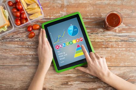 alimentacion balanceada: alimentaci�n saludable, vitaminas, dieta, la tecnolog�a y la gente concepto - cerca de manos de la mujer con la computadora Tablet PC y los alimentos en un recipiente de pl�stico en la mesa de contar las calor�as en el hogar