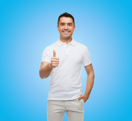 happiness or success: happiness, success, gesture and people concept - smiling man showing thumbs up over blue background