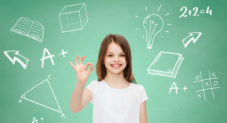 advertising, school, education, childhood and people - smiling little girl in white t-shirt showing ok sign over green board with doodles background Stock Photo