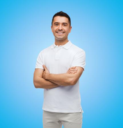 행복과 사람들이 개념 - 파란색 배경 위에 교차 팔을 가진 흰색 티셔츠에 웃는 남자 스톡 콘텐츠