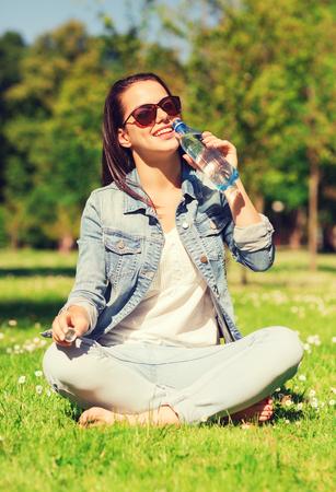 tomando agua: estilo de vida, verano, vacaciones, bebidas y concepto de la gente - la chica joven sonriente en gafas de sol con la botella de agua sentado en el c�sped en el parque Foto de archivo