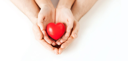 love confession: health, love and relationships concept - closeup of couple hands with big red heart