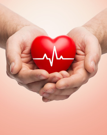 hands holding heart: family health, charity and medicine concept - close up of hands holding red heart with cardiogram over beige background