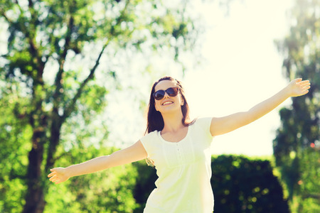 summer, leisure, vacation and people concept - smiling young woman wearing sunglasses standing in park Stock Photo