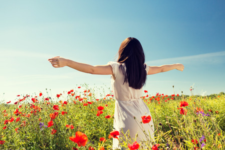 red poppies on green field: happiness, nature, summer, vacation and people concept - young woman dancing on poppy field from back