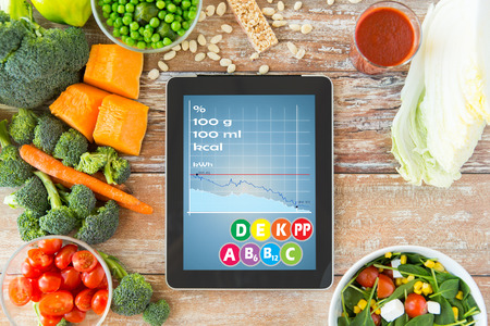 alimentacion balanceada: la alimentación saludable, la dieta, las calorías contando y pesar concepto de pérdida - cerca de la pantalla de Tablet PC con la carta y verduras en la mesa Foto de archivo