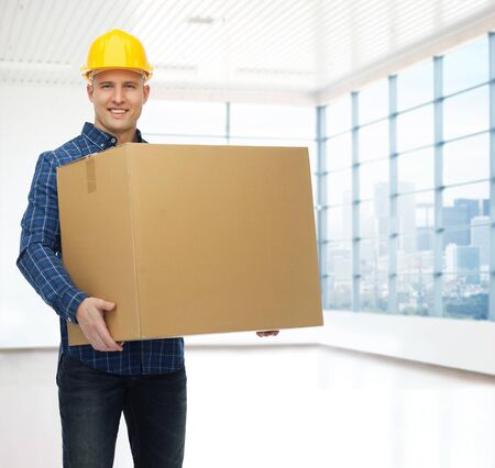 repair, construction, building, people and maintenance concept - smiling male builder or manual worker in helmet carrying big cardboard box over empty flat background photo