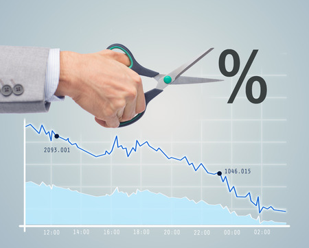 regress: business, people, default, financial and economical crisis concept - close up of businessman hand with scissors cutting percentage sign over chart and gray background
