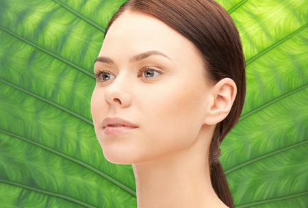 health, people, eco and beauty concept - beautiful young woman face over green palm leaf background Stock Photo