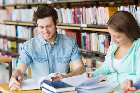 mensen, kennis, onderwijs en school concept - groep van gelukkige studenten met boeken voorbereiden om examen in de bibliotheek Stockfoto