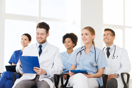 hospital, profession, people and medicine concept - group of happy doctors on seminar in lecture hall at hospital photo