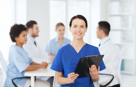 medics: clinic, profession, people and medicine concept - happy female doctor or nurse with clipboard over group of medics meeting at hospital