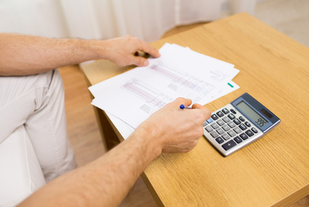business savings: business, savings, finances and people concept - close up of man hands with papers and calculator at home